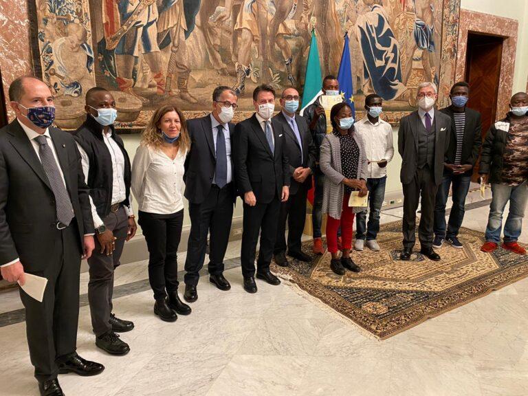 Alla vigilia dello stop ai decreti Salvini, Conte consegna permessi soggiorno alla vedova e ai compagni di lavoro di Thomas Daniel, l'operaio morto in cantiere